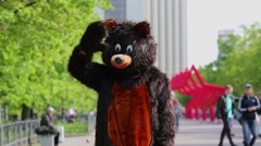 Actor dressed in bear costume stands on alley at park and waves Stock Footage