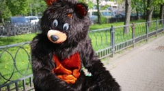 Stock Video Footage of Actor dressed in bear costume sits at park and waves his hand.