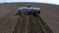 Tractor with planter cultivates land in a field. Aerial footage Stock Footage