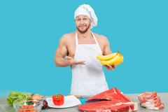 chef in a white apron holding meat and bananas - stock photo