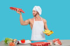 Chef in a white apron holding meat and bananas Stock Photos