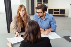 Young couple discussing investments with a broker - stock photo