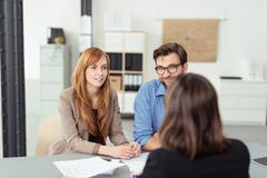 Investment broker meeting with a young couple - stock photo