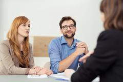 Broker having a discussion with a young couple - stock photo