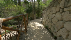 Stock Video Footage of Stone walls and thatched roof houses at Xcaret Park, Mexico