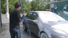 A man washing a car at the car wash self-service using foam - stock footage