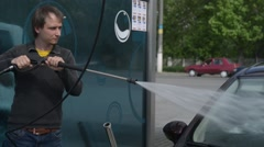 A man washing a car at the car wash self-service using foam and water washes foa - stock footage