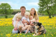 Happy Family and Pet Dog in Flower Meadow - stock photo