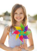 Happy girl with colorful pinwheel toy Stock Photos