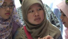 Young Muslim women speak at information desk, Kuala Lumpur, Malaysia Stock Footage