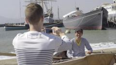 Tourist Takes Photos Of His Boyfriend In A Row Boat On Shore (4K) - stock footage