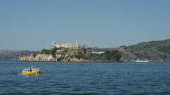 Small cruise ship passing by Alcatraz Island in San Francisco Stock Footage