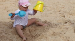 Little girl playing in the sand with a bucket and spade. - stock footage