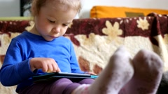 Little girl on a couch playing tablet computer game sliding touchscreen Stock Footage