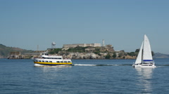Ferry and Sailboat passing by Alcatraz Island in San francisco Stock Footage
