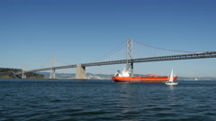 Cargo ship and Sailboat at the Oakland Bay Bridge in San Francisco Stock Footage