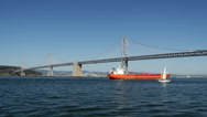 Stock Video Footage of Cargo ship and Sailboat at the Oakland Bay Bridge in San Francisco