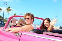 Couple happy in vintage retro car - Friends driving on summer road trip - stock photo