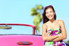 Car woman driver happy smiling by pink vintage convertible - stock photo