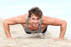 Fitness man exercising push ups - male athlete doing push-up Stock Photos