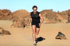 Runner running - Man sprinting in desert training Stock Photos