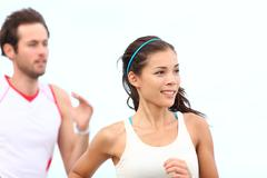 Runners jogging - Young couple running outside training for marathon - stock photo