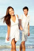 Beach couple happy holding hands -  Young beautiful couple walking on beach - stock photo