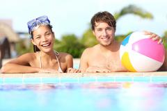 Summer vacation couple having fun in pool on sunny day in tropical resort Stock Photos