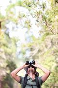 Binoculars - man hiker looking up at copy space during outdoors hiking trip Stock Photos