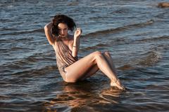 seminude woman against sea background - stock photo