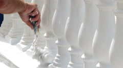 Hand painter painting or whitewashing white Andalusian balustrade in boardwalk. - stock footage