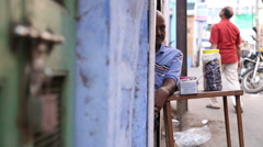 One side portrait of Indian man sitting by table at street while people pass. Stock Footage