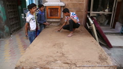 Indian boys realigning sand with a trowel at street in Jodhpur. Stock Footage
