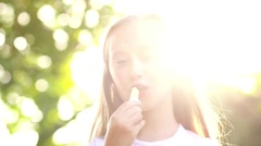 Adorable little girl with lolly, sunshine Stock Footage