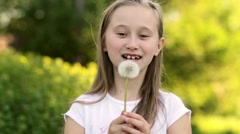 Beautiful child blowing away dandelion flower in spring - stock footage