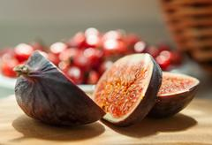 Chopped Fig fruits on the cutting board with briar (dog rose) on the plate - stock photo