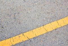 Road asphalt texture and yellow line - stock photo