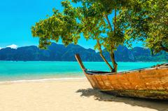 Wooden boat on sandy shore of exotic beach Stock Photos