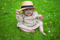 Beautiful baby girl wearing a sun hat in the park Stock Photos