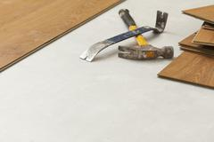 Worn Hammer and Pry Bar with Laminate Flooring Abstract with Copy Room. - stock photo