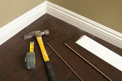 Stock Photo of Hammer, Laminate Flooring and New Baseboard Molding Abstract.