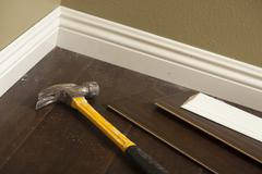 Hammer, Laminate Flooring and New Baseboard Molding Abstract. Stock Photos