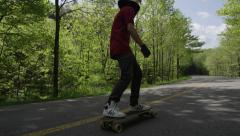Extreme Sport Longboard Racers on forest hill road - Downhill Skateboarding Stock Footage