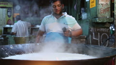 Man talking on phone before pouring ingredient to kettle with boiling chai. Stock Footage