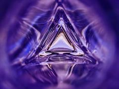 Stock Photo of Abstract image of the inside of a triangle glass bottle purple color background