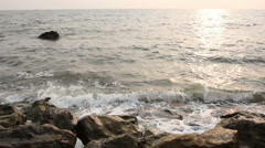 Waves breaking on rocks sunset Stock Footage