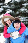 Young happy winter couple doing piggyback having fun outside in winter snow Stock Photos