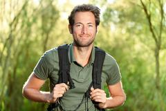 Young man hiking - Male hiker walking in forest - stock photo