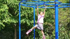 Determined Asian Girl Attacks The Monkey Bars At The Playground Stock Footage