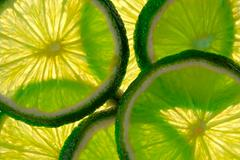 Green lime overlapped slices close-up background. Stock Photos